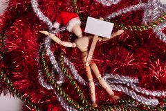 Blank sign held by wooden jointed manikin doll laying on red silver mess of shimmering garland wearing a Santa Claus Hat. Blank picket sign held by wooden royalty free stock photos