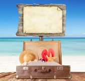 Blank sign with old suitcase on wooden planks Stock Photo