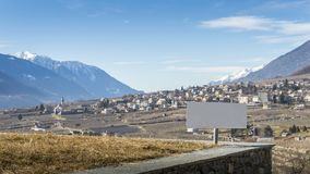 Blank sign overlooking vineyards above Sondrio, an Italian town and comune located in the heart of the wine-producing. Blank sign overlooking vineyards above royalty free stock photography