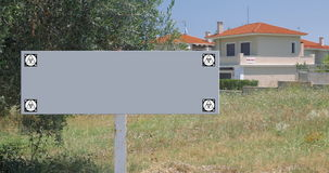 Blank sign of real estate advert. Blank signboard with house for sale in background. Copy space for real estate advertising. Chroma key with tracking motion stock footage