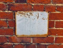 Blank sign on red brick wall. Blank or empty weathered and corroded sign mounted onto a red brick wall with space for copy. Mitcham Stock Images