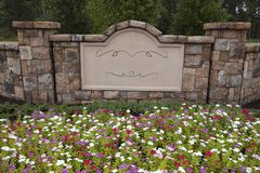 Blank Sign in Rock Wall Surrounded by Flowers and Trees royalty free stock images