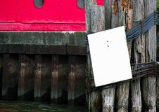 Blank sign on pier piling Royalty Free Stock Photo