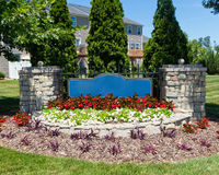 Blank sign of the subdivision entrance. Blank sign of the town homes subdivision entrance with summer flowers Stock Image