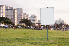 Blank sign in urban park at dusk Royalty Free Stock Photo