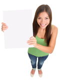 Blank sign woman isolated. Sign woman smiling standing isolated. Top view of multi ethnic girl showing blank empty sign board with copy space for text message Royalty Free Stock Photos