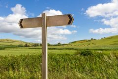 Blank Wooden Sign. A blank wooden directional sign against a sunny blue sky royalty free stock images