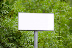 Blank sign in the woods. Blank white sign in front of forest trees Stock Photo