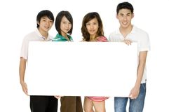 Blank Signboard. Four young asian adults holding a blank sign for text stock images