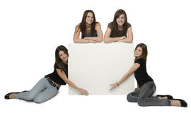 Blank signboard. Four teen girls placed around large empty signboard. Isolated on white Royalty Free Stock Photo