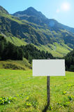 Blank signboard in a lush mountain valley Royalty Free Stock Photography