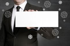 Blank signboard and snowflakes is held by businessman Stock Photo