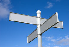 Blank Signpost. With four direction pointers against a blue sky royalty free stock image