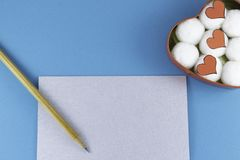 A blank silver letter with a wooden pencil and a heart-shaped box with cotton balls and hearts inside on a blue background. Letter or invitation Minimalist stock image