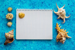 Blank sketchbook on the blue crystal background and seashells. Top view. Mock-up template for design Royalty Free Stock Image