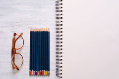 Blank sketchbook with color pencils and glasses Royalty Free Stock Photos