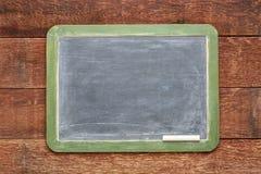 Blank slate blackboard against rustic wood Royalty Free Stock Photos