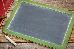 Blank slate blackboard with chalk and books Royalty Free Stock Photography