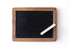 Blank slate and a white chalk. Over its wooden frame royalty free stock images