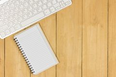 Blank small book and keyboard on wooden of brown, top angle view. Copy space, for presentation Royalty Free Stock Photography