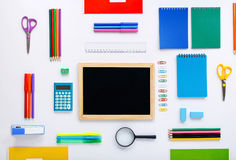 Blank small chalkboard with group of school supplies. On a white background. Flat lay, top view Stock Photos