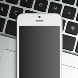 blank smart phone on the laptop Royalty Free Stock Image