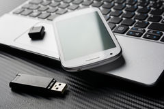 Blank Smartphone With Green Reflection Lying On Business Notebook Keyboard Next To An USB Storage, All Above A Carbon Layer Royalty Free Stock Photography
