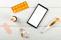 Blank smartphone with medical items on the desk Royalty Free Stock Images