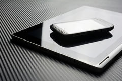 Blank Smartphone With Reflection Lying On Business Tablet With Reflection On Carbon Background Stock Images