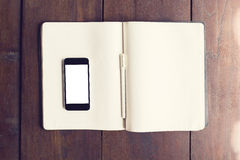 Blank smartphone screen on blank page of diary with pen on woode Royalty Free Stock Photos