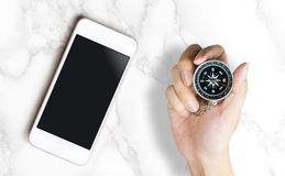 Blank smartphone screen with hand on compass for GPS mobile application Stock Photos
