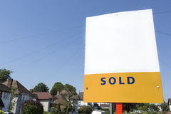 Blank SOLD sign outside a street full of houses on a bright day Stock Photos