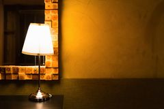 Table lamp shining warm light on grunge wall. Blank space of dirty grunge wall shined by vintage table lamp on black desk beside mirror which decorated inside royalty free stock photos