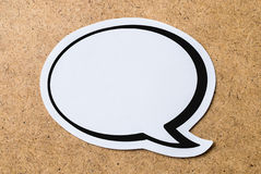 Blank speech bubble. Large blank speech bubble on a light brown wooden cork board background. Chat bubble cut from paper and cardboard. Message, chat and Royalty Free Stock Images