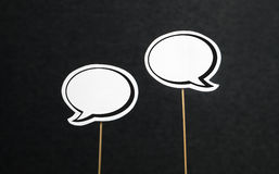 Blank speech bubbles. 2 blank speech bubbles on a dark black background. Chat bubble cut from paper with wooden stick. Fun discussion, protesting and commenting Royalty Free Stock Photos