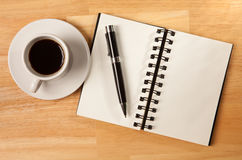 Blank Spiral Note Pad, Cup and Pen on Wood. Blank Spiral Note Pad, Cup of Coffee and Pen on Wood Background Royalty Free Stock Images