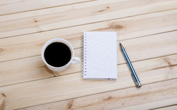 Blank Spiral Note Pad, Cup and Pen on Wood. Checkered Spiral Notepad, Cup Of Coffee And Pen On Wooden Desk Stock Photo