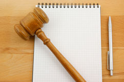 Blank spiral note pad and gavel. On wooden table Stock Image