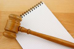Blank spiral note pad and gavel. On wooden table Royalty Free Stock Image
