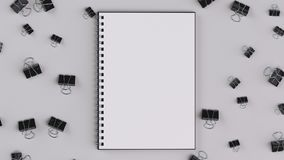 Blank spiral notebook with black binder clips on white table. Business, education or office mockup. 3D rendering illustration Royalty Free Stock Image