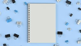 Blank spiral notebook with black, white and blue binder clips on blue table. Business, education or office mockup. 3D rendering illustration Royalty Free Stock Image