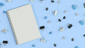 Blank spiral notebook with black, white and blue binder clips on blue table. Business, education or office mockup. 3D rendering illustration Royalty Free Stock Photography