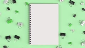 Blank spiral notebook with black, white and green binder clips o. N green table. Business, education or office mockup. 3D rendering illustration Stock Image