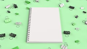Blank spiral notebook with black, white and green binder clips o. N green table. Business, education or office mockup. 3D rendering illustration Royalty Free Stock Image