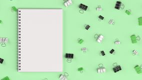 Blank spiral notebook with black, white and green binder clips o. N green table. Business, education or office mockup. 3D rendering illustration Royalty Free Stock Images
