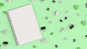 Blank spiral notebook with black, white and green binder clips o. N green table. Business, education or office mockup. 3D rendering illustration Royalty Free Stock Photos
