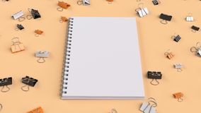 Blank spiral notebook with black, white and orange binder clips. On orange table. Business, education or office mockup. 3D rendering illustration Royalty Free Stock Images