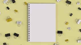 Blank spiral notebook with black, white and yellow binder clips. On yellow table. Business, education or office mockup. 3D rendering illustration Stock Photo