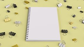 Blank spiral notebook with black, white and yellow binder clips. On yellow table. Business, education or office mockup. 3D rendering illustration Royalty Free Stock Image
