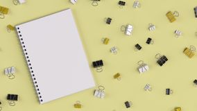 Blank spiral notebook with black, white and yellow binder clips. On yellow table. Business, education or office mockup. 3D rendering illustration Stock Images